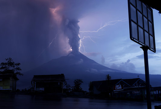 Lightning strikes as Mount Merapi volcano erupts spewing out towering clouds of hot gas and debris, as seen from Ketep village in Magelang