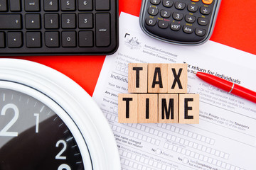 Tax Time - Australia - wooden letters with Tax Form, clock, keyboard and calculator