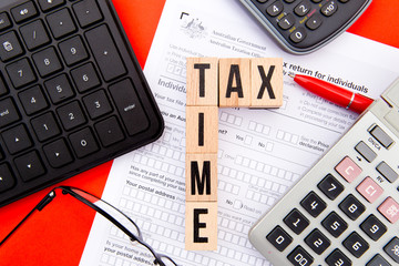 Tax Time - Australia - wooden letters with Tax Form, eyeglasses, keyboard and calculator