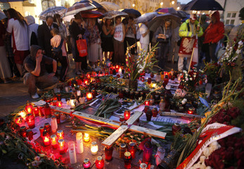 Supporters of the late Polish President Lech Kaczynski gather and pray at the wooden cross in front of Presidential Palace in Warsaw