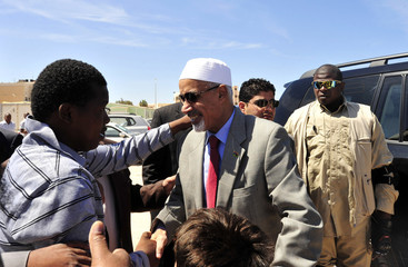 Libyan National Congress President Magarief greets refugee boys during a visit to the Tawergha refugee camp in Benghazi