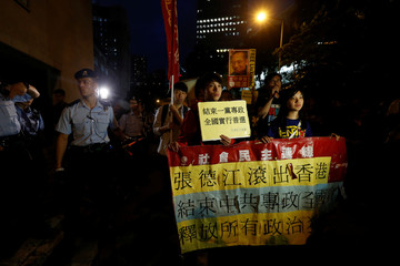 Protesters march with a banner urging Zhang Dejiang, the chairman of China's National People's Congress, to leave Hong Kong