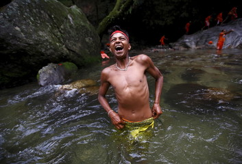 """A devotee reacts to cold water as he takes a dip while participating in the """"Bol Bom"""" pilgrimage in Kathmandu"""