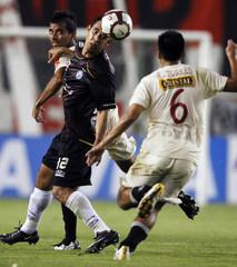 Ledesma of Lanus battles Torres and Espinoza of Universitario during their Copa Libertadores soccer match in Lima