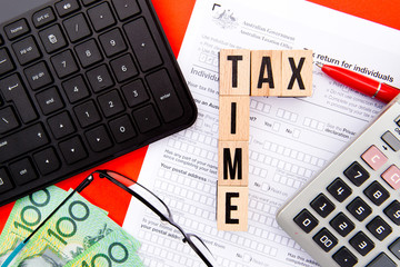 Tax Time - Australia - wooden letters with Tax Form, eyeglasses, money, keyboard and calculator