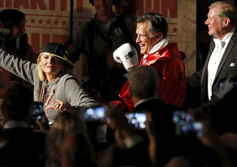 Mitt Romney is lead to the ring by his wife Ann Romney before he fights five-time heavyweight champion Evander Holyfield during a boxing match in Salt Lake City, Utah