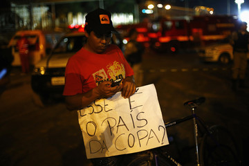 """A man holds a banner that reads """"This is the country of the cup?"""" next to a bridge that collapsed while under construction in Belo Horizonte"""