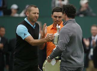 Joint runners-up in the British Open Championship Sergio Garcia and Rickie Fowler congratulate winner Rory McIlroy at the Royal Liverpool Golf Club in Hoylake