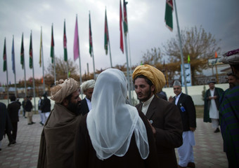 Members of the Loya Jirga, or grand assembly, prepare to leave after its closing ceremony in Kabul