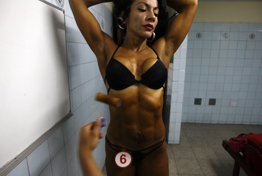 A competitor has tanning lotion applied on her body before her turn in a bodybuilding competition in Lima