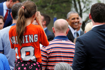 A young fan in a Peyton Manning jersey takes pictures as U.S. President Obama greets attendees after welcoming the Denver Broncos for a reception in Washington