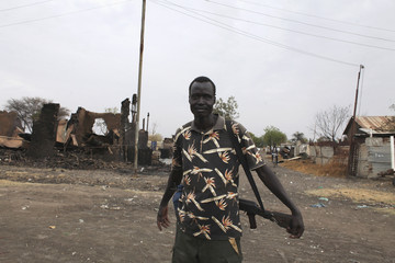 A member of anti-government forces who used to work as a teacher, holds his gun next to destroyed buildings in the town of Malakal, Upper Nile State