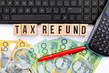 Tax Refund - Australia - wooden letters with keyboard, money and calculator