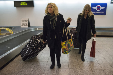 "A digital sign in the background reads ""Happy Holidays"" as women, arriving from Australia, pick up baggage from arrivals hall two-days ahead of Christmas at LaGuardia Airport in New York City"