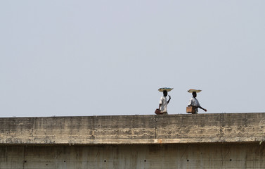Men walk across a bridge under construction in Nigeria's capital territory Abuja