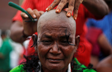A supporter of Tamil Nadu Chief Minister Jayaraman gets her head shaved near Jayalalithaa's burial site in Chennai