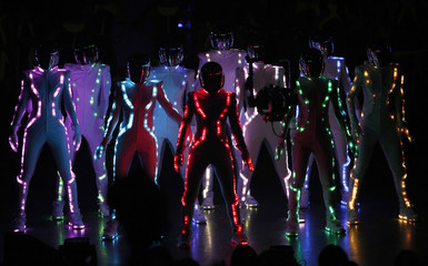 Dancers wearing illumination bodysuits perform with Japanese pop group E-girls at the MTV Video Music Awards Japan 2014 in Chiba