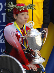 Tsuchida of Japan holds the trophy while listening to her national anthem after winning women's wheelchair divisions of 2011 Boston Marathon