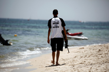 A tourist police member patrols near the beachside of the Imperial Marhaba hotel which was attacked by a gunman last year in Souss
