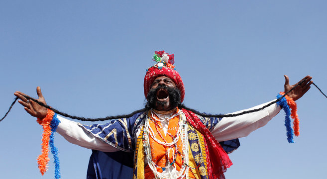 A man laughs as he shows his moustache during a competition at Pushkar Fair
