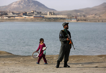 An Afghan girl walks past as a policeman stands at a check point in Qargha dam on the outskirts of Kabul