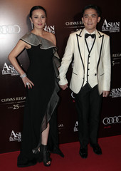 Hong Kong actor Tony Leung and his actress wife Carina Lau arrive for the Asian Film Awards in Hong Kong