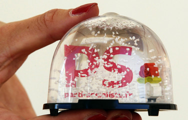 A woman holds a snow globe with the logo of the French Socialist Party on a stand during the summer meeting of the French Socialist Party in La Rochelle