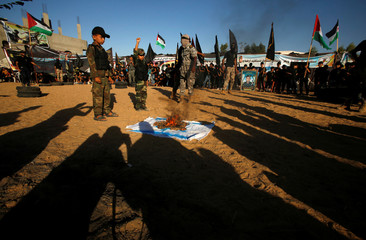 Palestinians burn an Israeli flag  during a military-style graduation ceremony at a summer camp organized by the Islamic Jihad Movement in the southern Gaza Strip