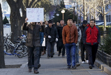 Tian Honglei (L), a migrant worker from Henan province, holds a placard as he marches with his fellow workers along a main street to protest against a construction site and demand their salaries, in central Beijing