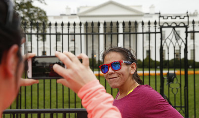 A woman wearing a pair of stars and stripes sunglasses gets her picture taken in front of the White House in Washington
