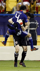 Japan's Yasuyuki Konno jumps into the arms of goalkeeper Eiji Kawashima's after scoring the winning penalty against South Korea in the penalty shootout of their 2011 Asian Cup semi-final soccer match at Al Gharafa stadium in Doha