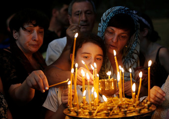 People light candles during a religious service marking the Day of the Virgin Mary at Sioni Cathedral in Tbilisi