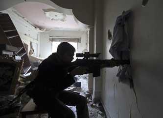 A  Free Syrian Army fighter fires his rifle during clashes in Haresta neighbourhood of Damascus