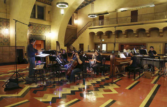 """Conducter Lowenstein leads the orchestra during a dress rehearsal for the experimental opera """"Invisible Cities"""", which is presented inside the historic Los Angeles Union Station in California"""