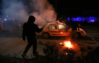 A protester videos a police car set on fire by protesters in Ferguson