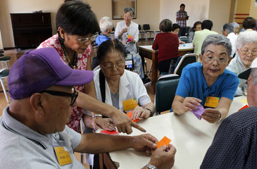 Members of the Japanese community in Peru make origami cranes to support Japan's earthquake and tsunami victims in Lima