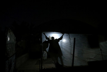Palestinian man fixes the cover of a makeshift mosque in Beit Lahiya town in the northern Gaza Strip