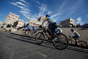 Members of a cycling team ride their bikes in the old quarter of Sanaa, the capital city of war-torn Yemen