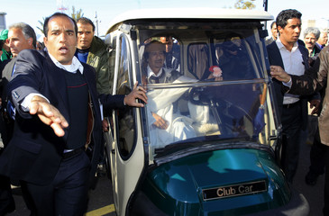 Libyan leader Muammar Gaddafi drives his personal cart in Tripoli after making a speech