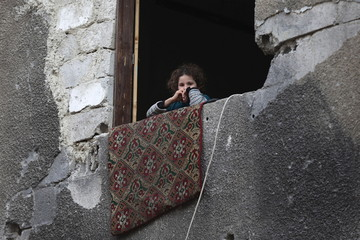 A girl looks out the window of a damaged building in Douma, Syria