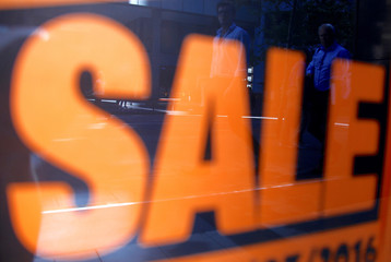 Shoppers are reflected in the window of a retail store displaying sales posters in central Sydney, Australia