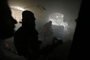 Palestinian fire-fighters extinguish a fire in a house which police said was hit in an Israeli air strike, in Gaza Strip