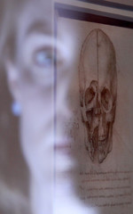 """Employee Alice Ross reflection is illuminated as she poses with artist Leonardo da Vinci's drawing """"A skull sectioned, 1489"""" at the Queen's Gallery at Buckingham Palace in London"""
