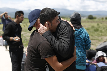 Refugees hug one another as a group of refugees leaves for another camp at a makeshift camp for migrants and refugees near the village of Idomen