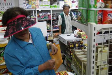 Lee Jin-taek looks at a customer at his general store in Seoul