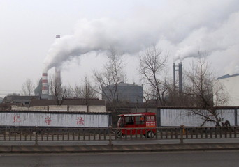 A motorcyclist rides past a steel firm in Linyi