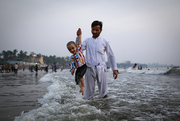 Arafat helps his 3-year-old son Meraj as he gets drenched in a wave on a beach along the Arabian Sea in Mumbai