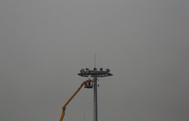 A worker maintains a street light at Tiananmen Square among smog during a polluted day in Beijing