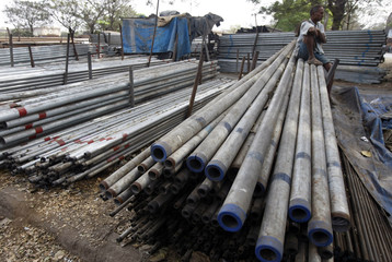 A worker rests on steel pipes at a steel market in Mumbai