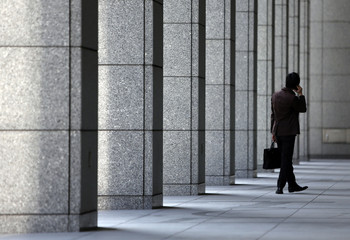 A man using his mobile phone walks past an entrance of a building at a business district in Tokyo